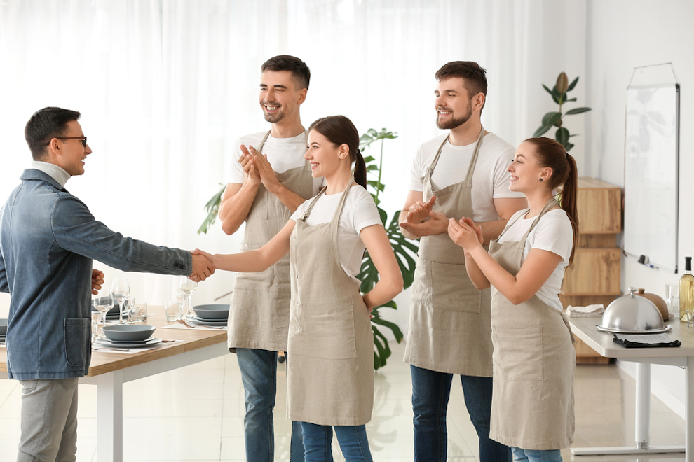 Teacher congratulating young people on successful completion of professional waiter courses